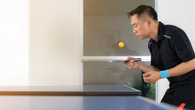Stół do ping-ponga, mężczyzna grający w tenisa stołowego z rakietą i piłką w hali sportowej
