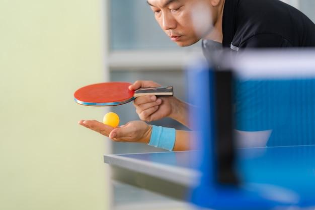 Stół do ping ponga, mężczyzna grający w tenisa stołowego z rakietą i piłką w hali sportowej