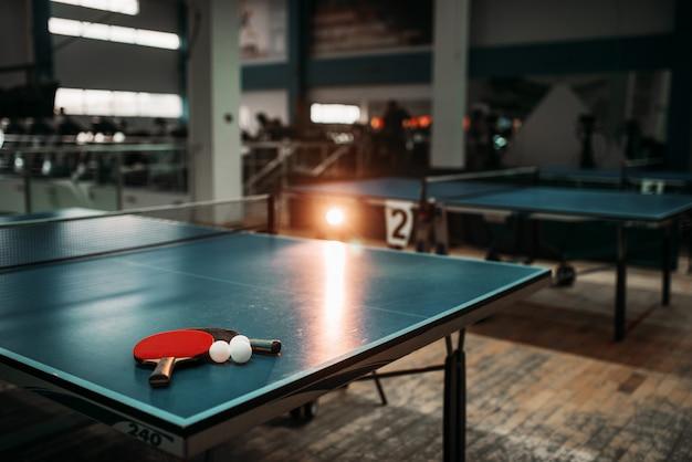 Stół do ping ponga z rakietami i piłeczkami w hali sportowej