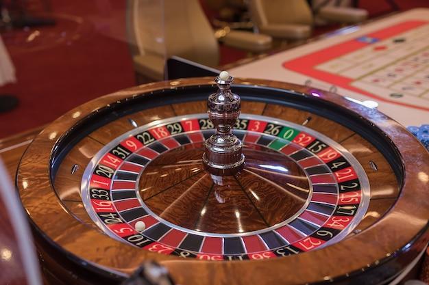 Stół do ruletki w kasynie, z wieloma grami i automatami, koło ruletki na pierwszym planie. złote i luksusowe światło, wnętrze kasyna. hazard to obstawianie pieniędzy lub granie w gry losowe na pieniądze