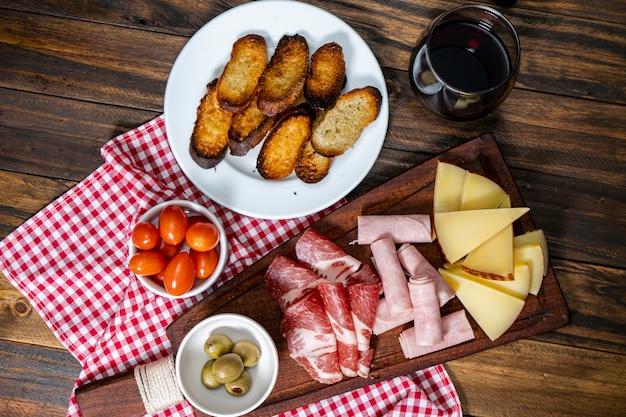 Stół do serów i wędlin, pomidorki koktajlowe, oliwki. widok z lotu ptaka.
