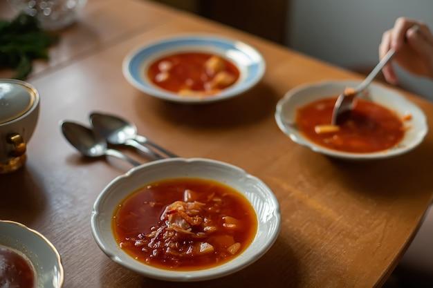 Stół do serwowania obiadów w rodzinie. kuchnia ukraińska. barszcz czerwony do zupy w białych talerzach.