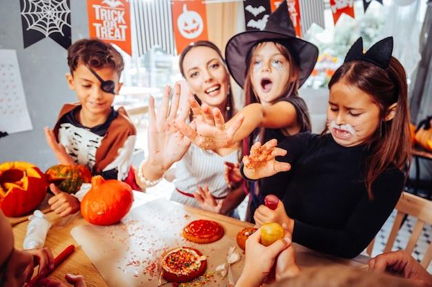 Stół do uroczystości. rozpromieniona matka i dzieci z pomalowanymi twarzami czują się szczęśliwi przygotowując stół na halloween