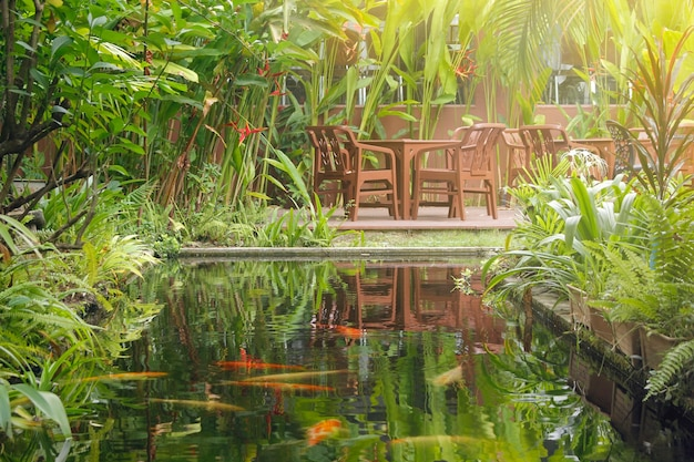 Stół i krzesła w ogrodzie otoczone pięknymi drzewami.