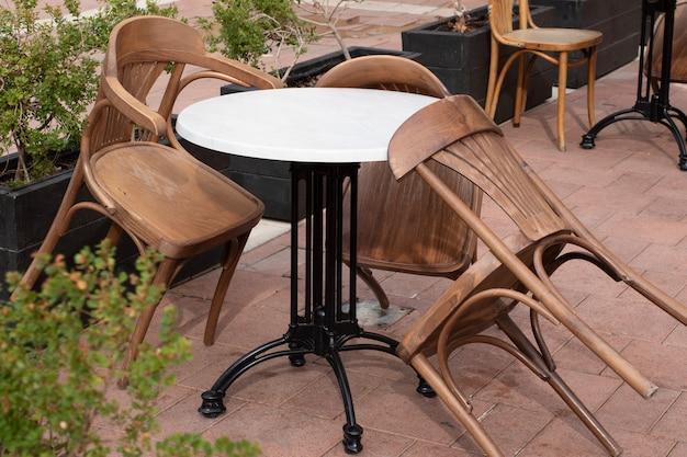 Stół i krzesła w zamkniętej kawiarni na ulicy.