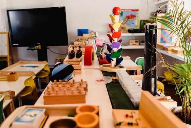 Stół i półki z materiałem montessori, kolorowe przedmioty i drewniane cylindry do badania