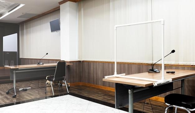 Stół konferencyjny z przezroczystą plastikową przegrodą zapobiegającą covid19