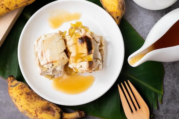 Stół kuchenny z grillowanymi bananami na deser z syropem miodowym, widok z góry.