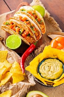 Stół meksykański z nachos, guacamole, tacos i składnikami. meksykańskie chipsy taco i nacho tortilla na drewnianych deskach. latynoskie jedzenie meksykańskie?