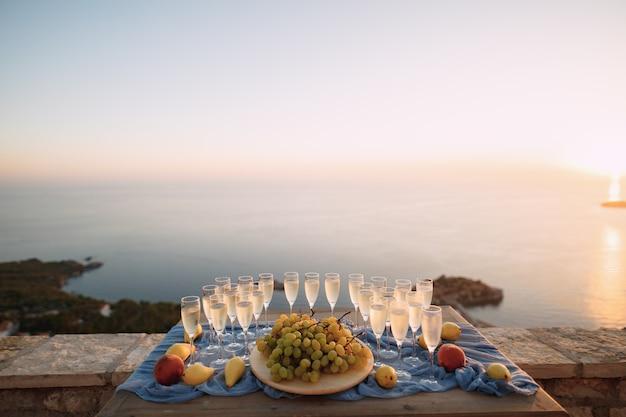 Stół nakryty na uroczystość z czystymi pustymi kieliszkami do szampana, talerz z białymi winogronami