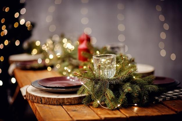 Stół noworoczny serwowany na uroczysty obiad. boże narodzenie ustawienie na drewnianym stole z dekoracyjnymi talerzami i kieliszkami do wina i czerwonymi świecami na szarym tle niewyraźne bokeh