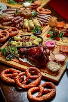Stół obiadowy oktoberfest z grillowanymi kiełbaskami mięsnymi, ciastem precla, ziemniakami, sałatką z ogórków, sosami, piwem