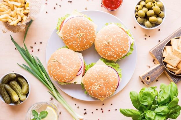 Stół obiadowy z burgerem, frytkami, warzywami, sosami, przekąskami i lemoniadą na drewnianym