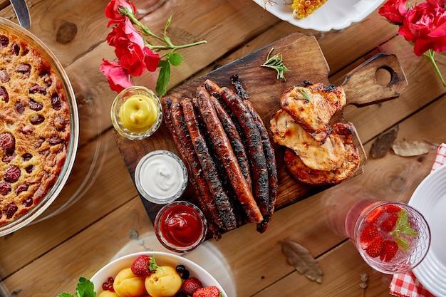 Stół obiadowy z grillem mięsnym, pieczonymi warzywami, sosami i lemoniadą, owoce, różnorodne przystawki podawane na imprezowym stole na świeżym powietrzu.