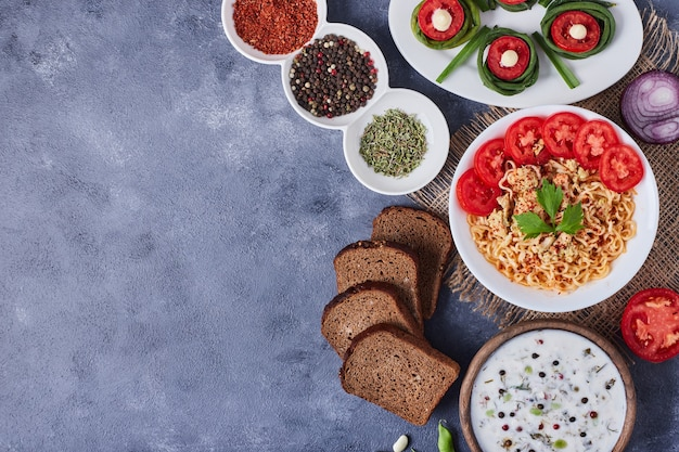 Stół obiadowy z mieszanymi potrawami w białych naczyniach na kawałku płótna.