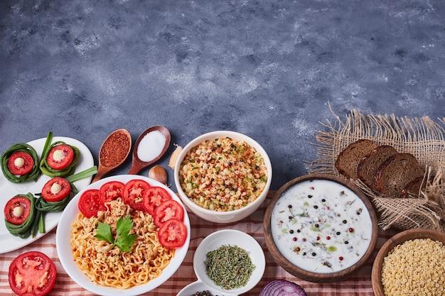 Stół obiadowy z mieszanymi potrawami w białych naczyniach.