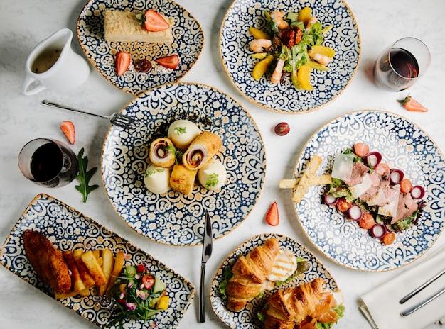 Stół obiadowy z mieszanymi potrawami.