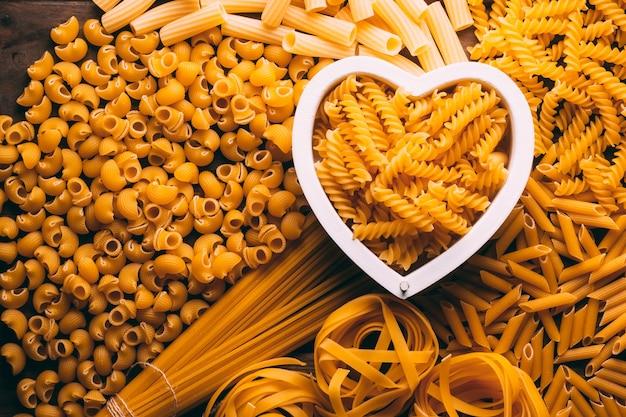 Stół pełen różnych rodzajów makaronów z sercem w środku, miłośnicy makaronów