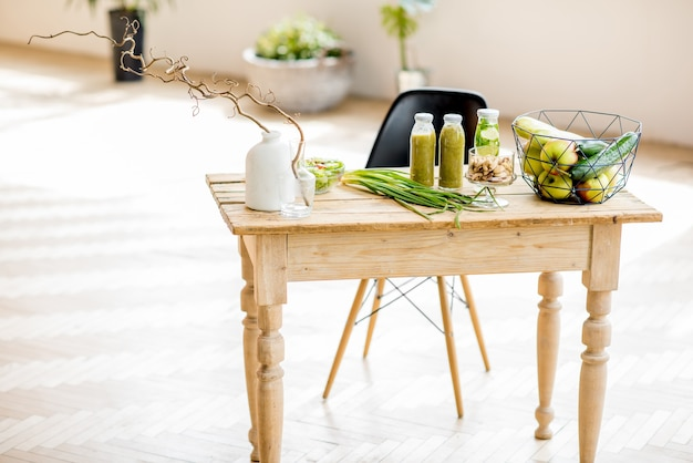 Stół pełen zdrowego zielonego jedzenia i koktajli w pięknym wnętrzu z zielenią