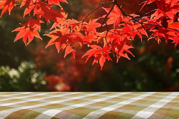 Stół piknikowy i całkowicie czerwone liście klonu jesienią.