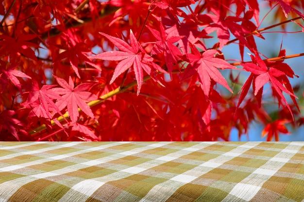 Stół piknikowy z całkowicie czerwonymi japońskimi liśćmi klonu.