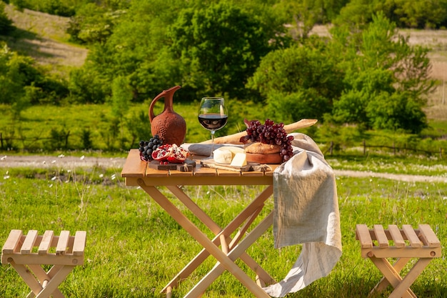 Stół piknikowy zastawiony czerwonym winem, serem, owocami, winogronami i chlebem stoi na łące w zielonej trawie
