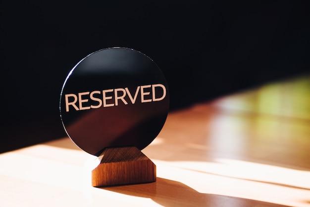 Stół restauracyjny zrestartowany przez klienta. rezerwacja znak na stole przeciw zamazanemu tłu
