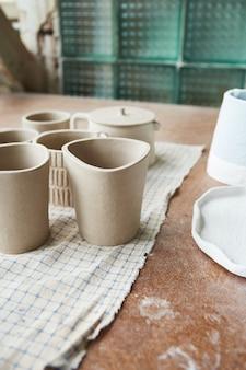 Stół roboczy ceramika. warsztat gliniany. proces tworzenia ceramiki. w jej pracowni pracuje mistrz ceramiki