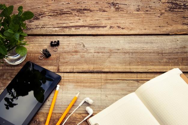 Stół roboczy z ekranem ipada, otwórz notatnik i zielone liście. copyspace. rustykalne drewniane. widok z góry.