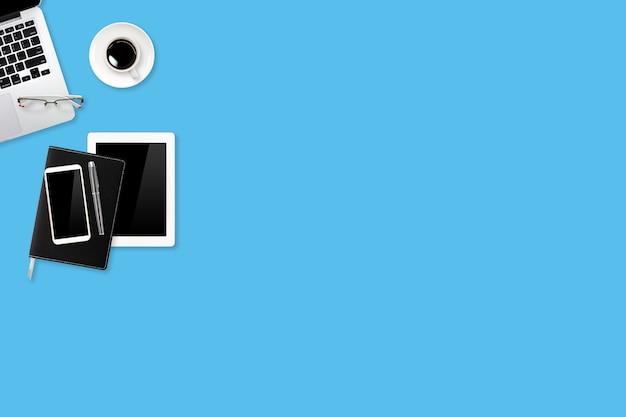 Stół roboczy z laptopa, materiałów biurowych, filiżanki kawy, telefonu komórkowego i filiżanki kawy na niebieskim tle pastelowych
