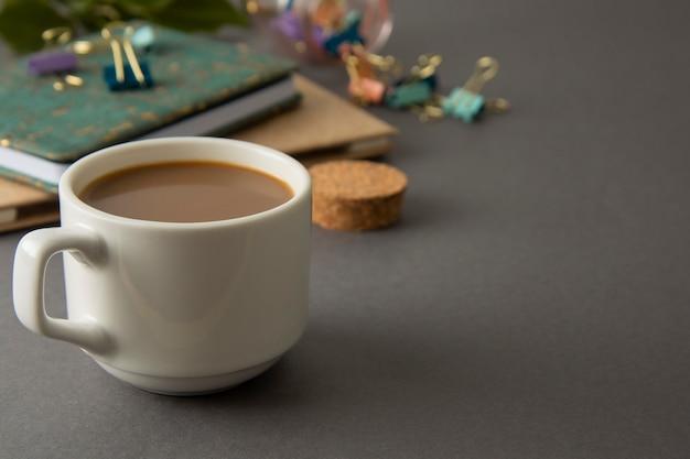 Stół roboczy z notatnikami, artykułami biurowymi i filiżanką kawy. szare tło. przestrzeń robocza.