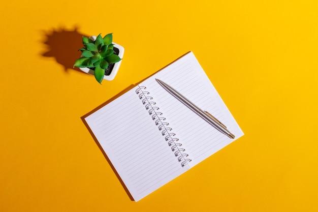Stół roboczy z otwartym notatnikiem i kwiatem na jasnożółtym tle