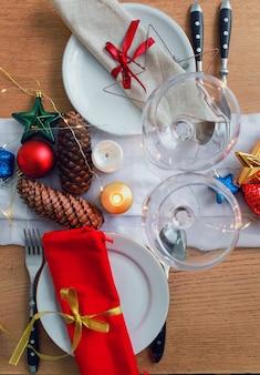Stół serwowany na świąteczny obiad w salonie. zbliżenie, ustawienie stołu, talerze, dekoracja gałęzi, świece i błyszczące zabawki na drewnianym stole tle