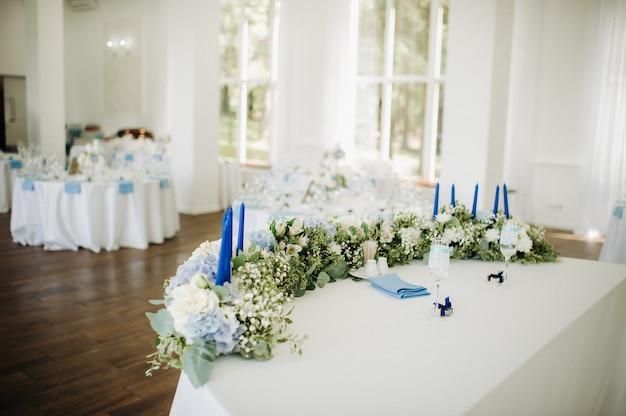 Stół ślubny panny młodej i pana młodego przyozdobiony mnóstwem kwiatów