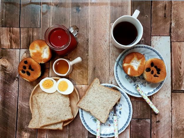 Stół śniadaniowy gotowane jajko rodzynki i kokosowe babeczki sok owocowy miód grzanki czarna kawa