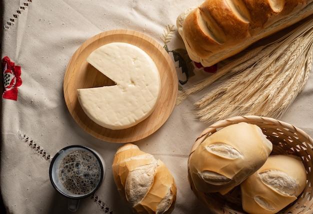 Stół śniadaniowy w brazylii z pieczywem, serem, filiżanką kawy i dodatkami na jasnym obrusie z haftem.