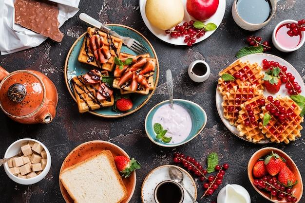 Stół śniadaniowy z goframi, kawą jogurtową i świeżymi owocami i jagodami