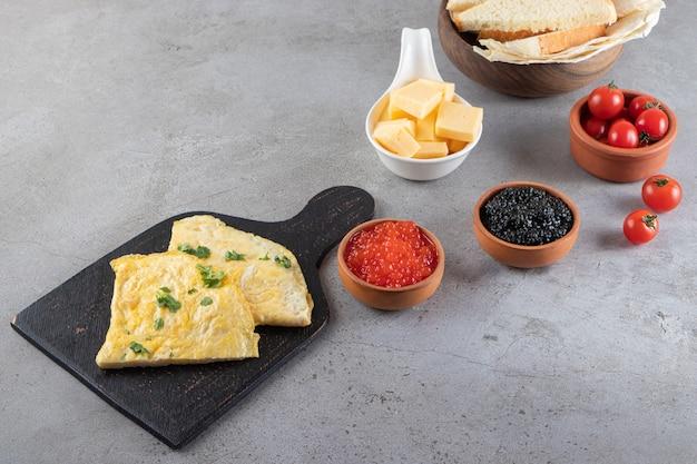 Stół śniadaniowy z omletem i kawiorem umieszczony na kamiennej powierzchni.