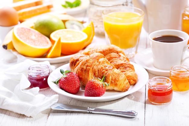 Stół śniadaniowy z rogalikami, kawą, sokiem pomarańczowym, tostami i owocami