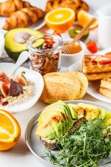 Stół śniadaniowy z tostem z awokado, płatkami owsianymi, goframi, rogalikami na białym tle