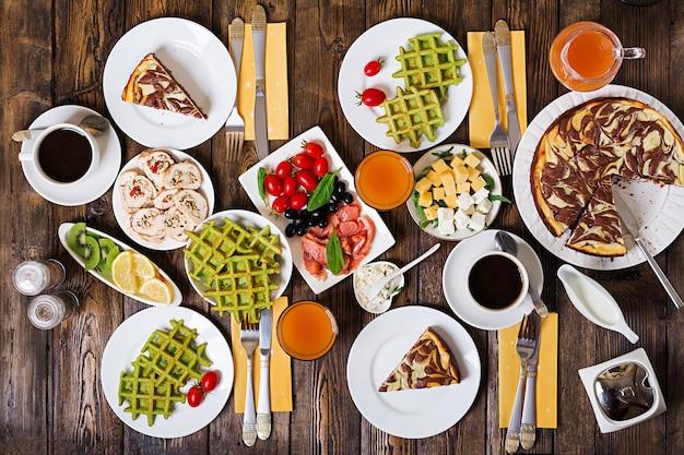 Stół śniadaniowy. zestaw świąteczny brunch, różnorodność dań z goframi szpinakowymi, łososiem, serem, oliwkami, roladkami z kurczaka i sernikiem. widok z góry. leżał płasko