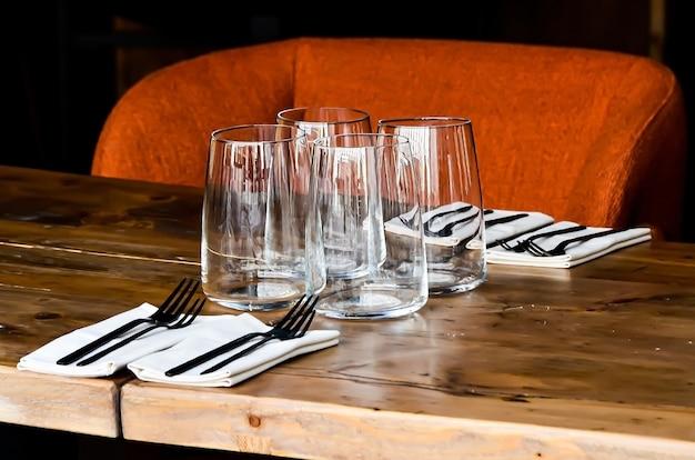 Stół w restauracji dla czterech osób: szklanki, serwetki i sztućce na drewnianym stole