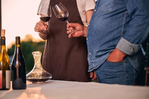 Stół w świetle słońca z butelek i karafki do wina. dwóch nierozpoznanych mężczyzn brzęczących okularami