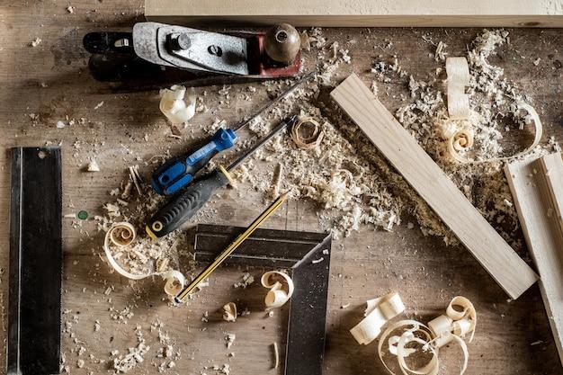 Stół warsztatowy z różnymi narzędziami ręcznymi w warsztacie do obróbki drewna lub stolarki, w tym dłuta, wkrętaki, taśma miernicza, ołówek, linijka