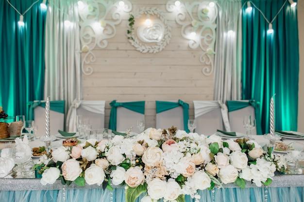 Stół weselny dla pana młodego i panny młodej, ozdobiony kompozycją kwiatową wykonaną z białych róż, w odcieniach seledynu