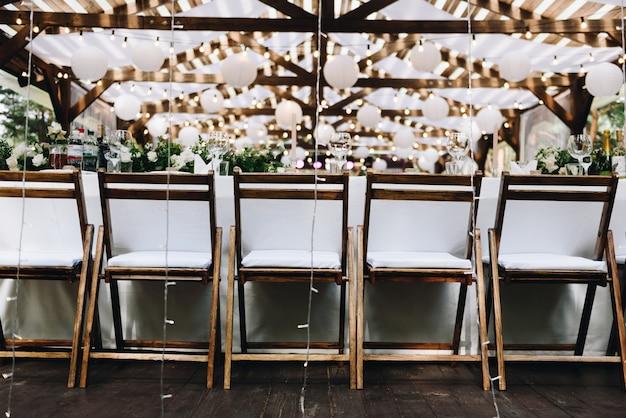 Stół weselny ozdobiony kwiatami i lampkami na stylowy ślub boho