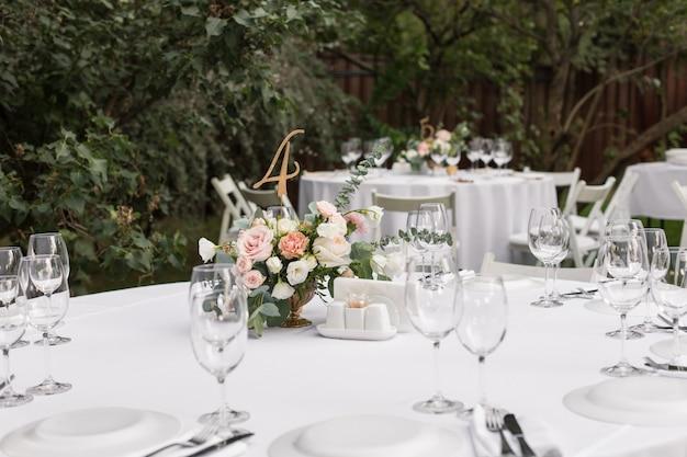 Stół weselny ozdobiony świeżymi kwiatami w mosiężnym wazonie. florystyka ślubna. stół bankietowy dla gości na zewnątrz z widokiem na zieloną przyrodę. bukiet z różami, eustomą i liśćmi eukaliptusa