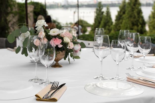Stół weselny ozdobiony świeżymi kwiatami w mosiężnym wazonie