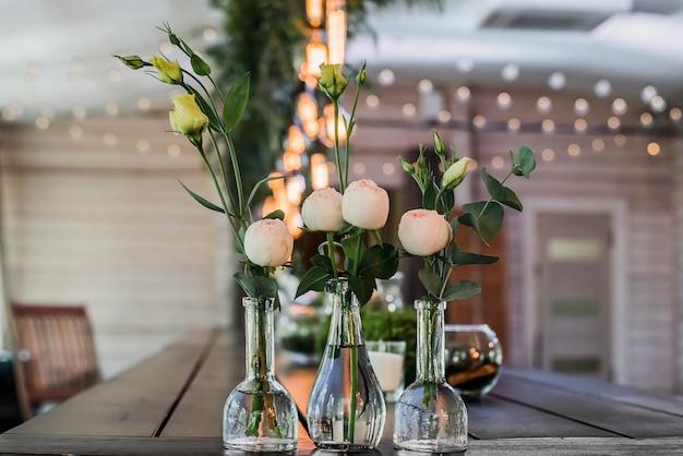 Stół weselny urządzony w stylu boho. ozdobiony detalami, układ piwonii w szklanych wazonach