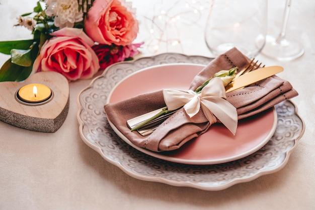Stół weselny ustawienie koncepcja talerz sztućce na lnianej serwetce i kwiaty z bliska stonowanych zdjęcie miękkie
